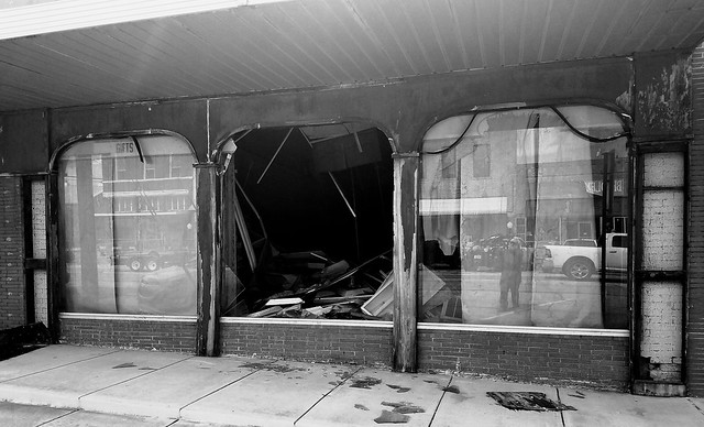 Tornado aftermath: store front with a busted window