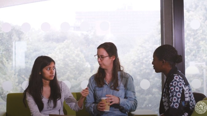 Three postgraduate students chatting at a table