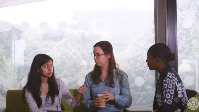 Three postgraduate students chatting at a table