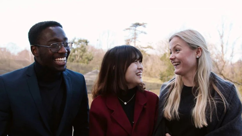 Three postgraduate students laughing outside