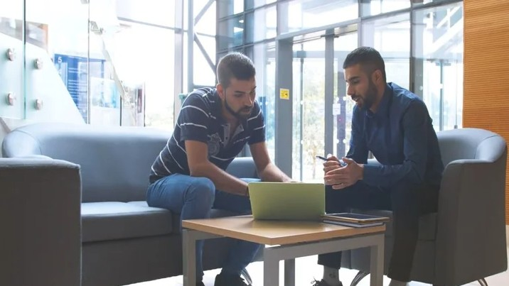 Two postgraduate students working together at a table