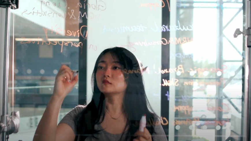 A postgraduate student writing on a clear whiteboard