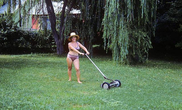 Mom mows our back yard while still wearing her bathing suit after returning from the beach. Not sure why she was doing it... mowing was always MY job. I would get $1.25 and usually spent it on a small size Vinnie's Pizza. Milford CT. August 1974