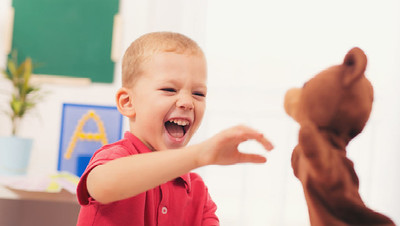Child in a classroom laughing at a puppet