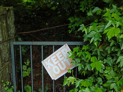 Keep out sign in an overgrown entrance gate