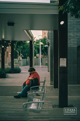 Man nodding off while waiting for a bus in Phoenix, Arizona.