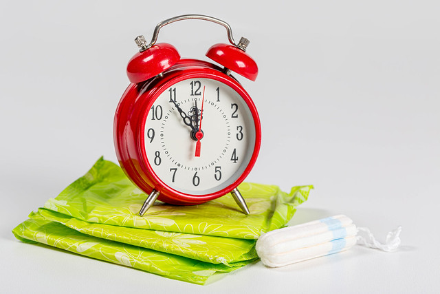 Alarm clock, pads and tampon on a white background. Concept of menstrual cycle, personal hygiene items