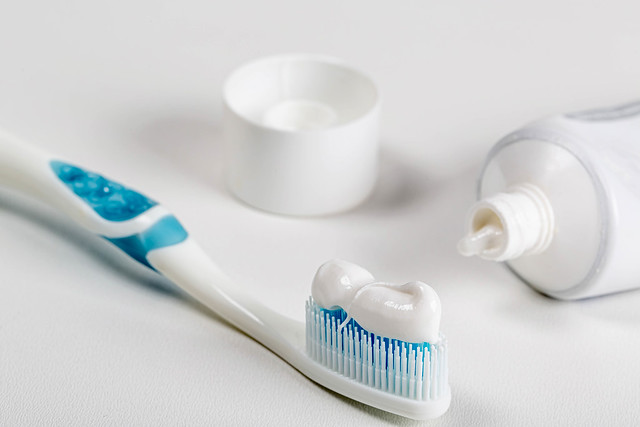 Dental brush with toothpaste on white background