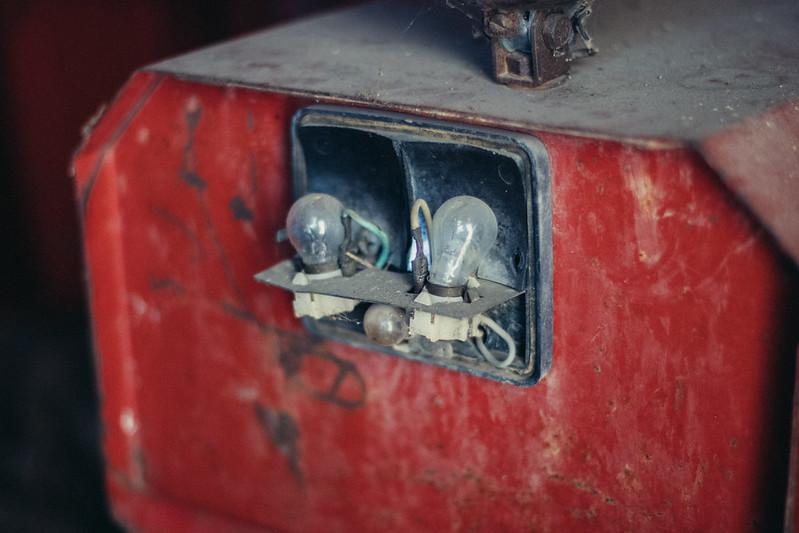 Tail light on a tractor with broken off cover and visible light bulbs