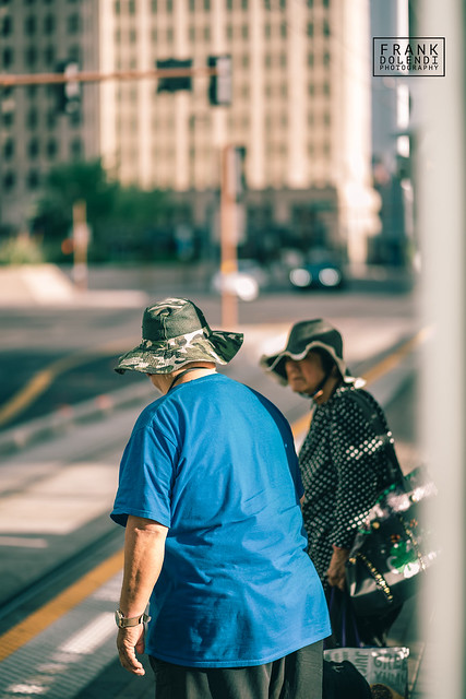 Husband and wife wait for the Metro Light Rail with matching camouflage sun hats in Downtown Phoenix, Arizona.