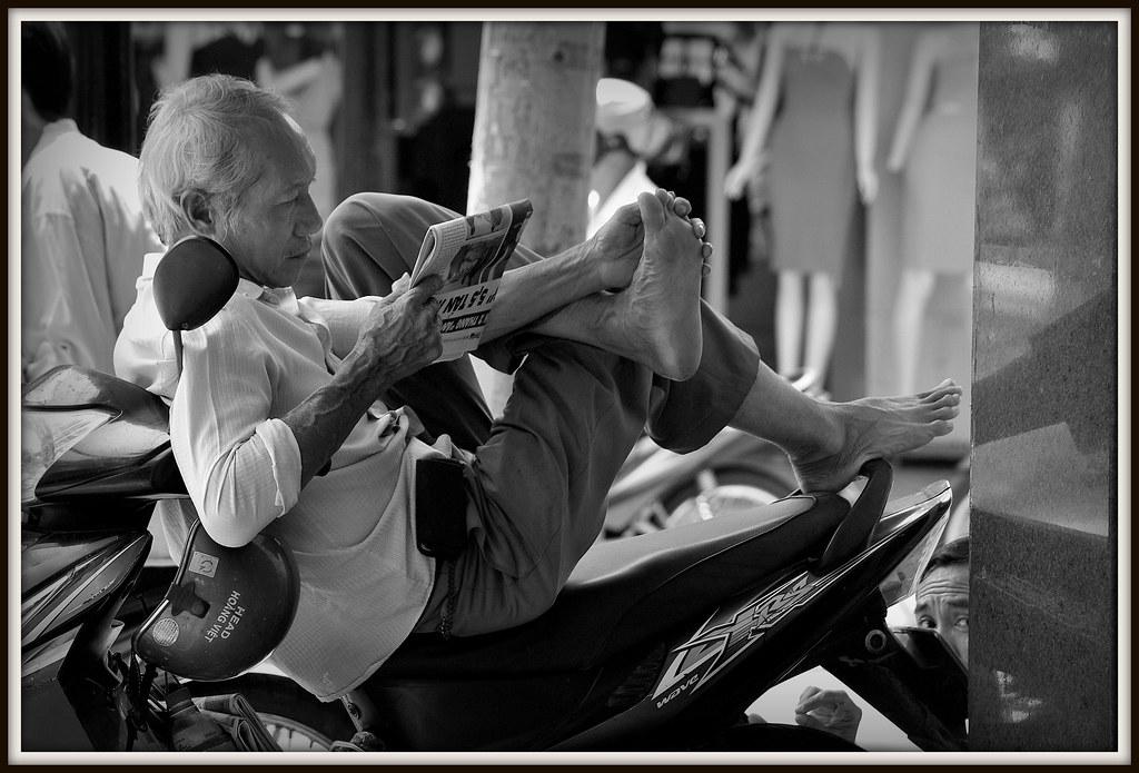 Pour lire le journal , se nettoyer entre les orteils en equilibre sur une motorbike aussi facilement , il faut faire preuve d'une sacrée dextérité.Rue de Saigon.