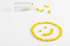 The concept of positive emotions from successful treatment or medical services. A smile made from yellow pills