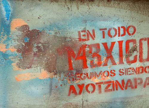 Protest graffiti on old grey stone posts that line the Paseo de la Reforma in Mexico City. It reads: En todo Mexico seguimos siendo Ayotzinapa