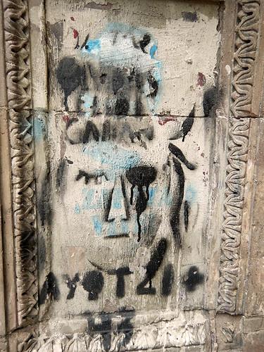 Protest graffiti on old grey stone posts that line the Paseo de la Reforma in Mexico City