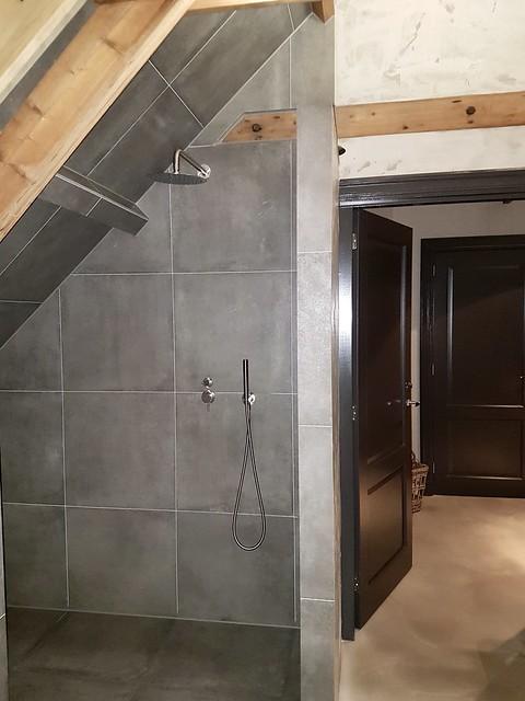 Grijze muurtegels balken badkamer