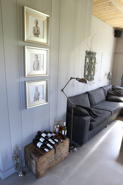 Hout muur woonkamer donkergrijze bank houten kist wijn trompet