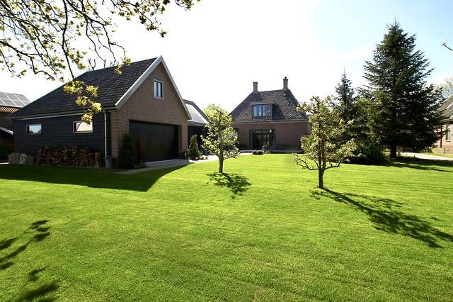 Landelijk verbouwde woning met gazon en houtopslag