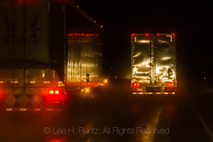 Semis on a Wet Road at Night