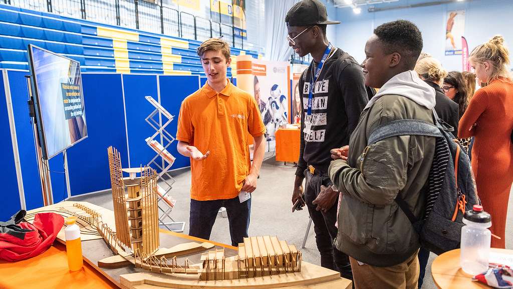Students demonstrating a model to visitors