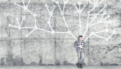 A young man standing in front of a wall with a interconnected lines painted on it