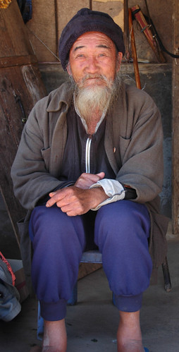 An old man in Laos wearing a furry hat