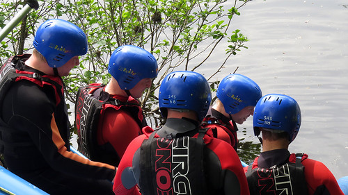 Rafters wearing blue helmets about to enter the water and navigate Horseshoe Falls in Llangollen, Wales