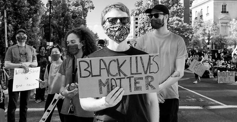 White, masked protester holding a Black Lives Matter sign