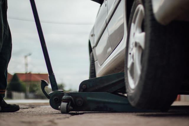Tire technician lifting a car with a car jack