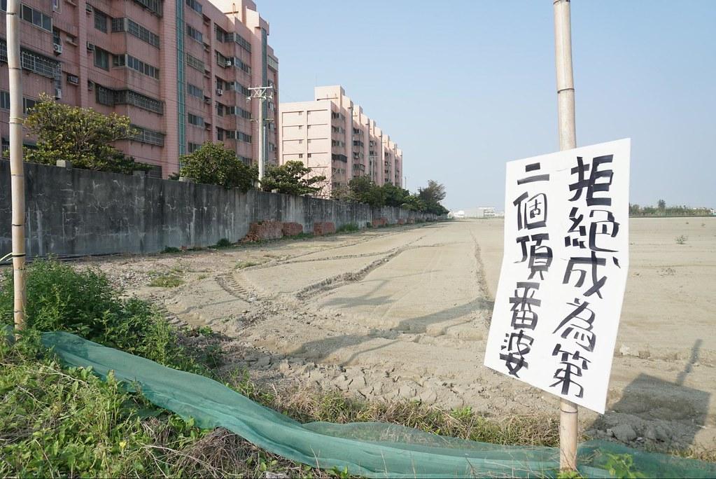 富麗大鎮與計畫開發的園區僅有一牆之隔,反對開發的居民在周遭張貼標語:「拒絕成為第二個頂番婆」(攝影:王章逸)