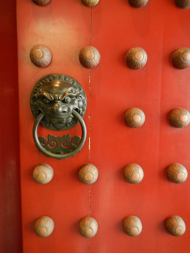 Brass lion door pull on the red door of a Chinese Temple in Singapore