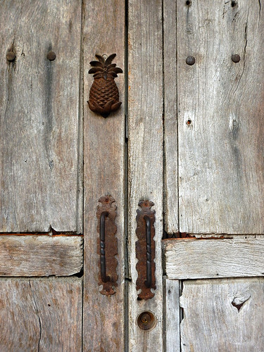 A weathered wood door in Bucerias, Mexico with a rusting pineapple knocker and door handles