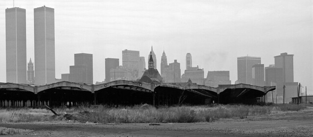 The point of no return. Weedy ruins of the Central Railroad of New Jersey terminal from 1913 graced by the elegant modernist form of the World Trade Center. Jersey City. November 1978.