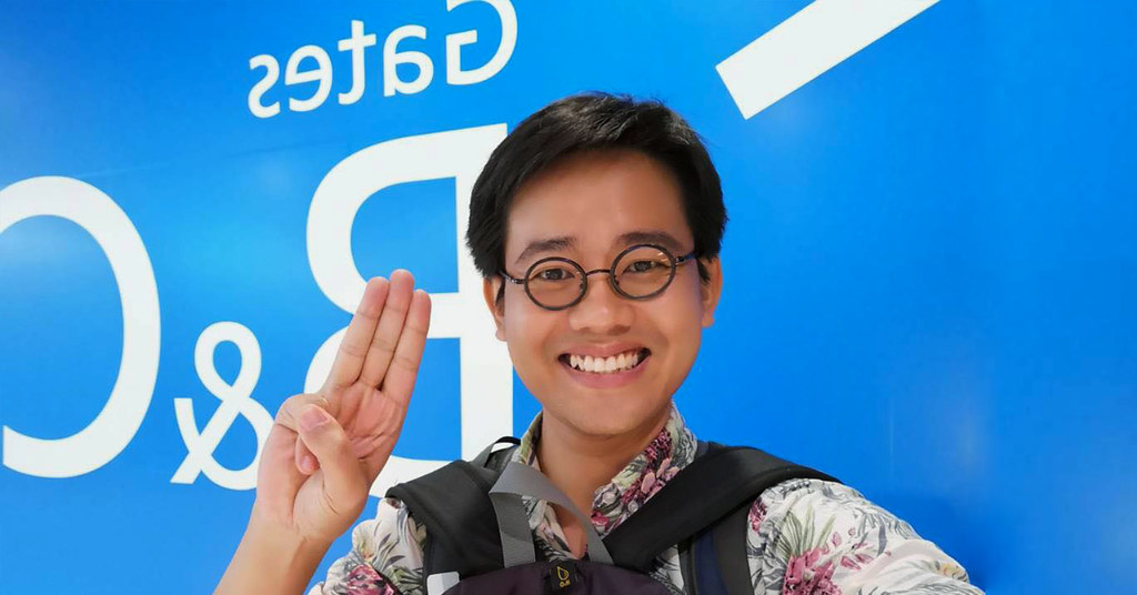 A portrait of Wanchalearm Satsaksit, standing in front of a blue and white background. He is a young man wearing a pair of round glasses and a floral-printed shirt, and smiling, while holding his right hand up in the three-finger Hunger Games salute.