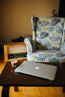 Coffee and Macbook in the living room with vintage armchair in the background. | by shixart1985