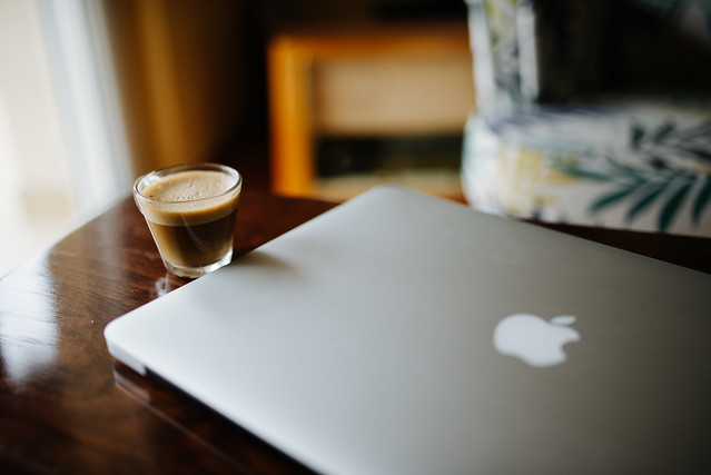 Coffee and closed Macbook on wooden table.