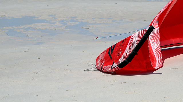Red sail on the beach