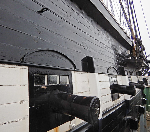 Cannons poking out of the exterior of the boat
