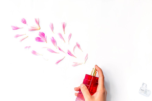 Floral scent concept. Perfume bottle in a woman's hand on a white background with peony petals | by wuestenigel