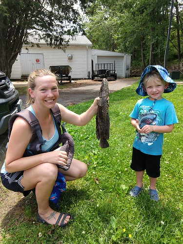 Young Ian Brainer admires his mom Sarah's snakehead catch