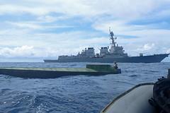 A U.S. Coast Guard Law Enforcement Detachment team member, embarked aboard USS Preble (DDG 88), boards a low profile go fast vessel (LPGFV) during an interdiction operation in the Eastern Pacific. (U.S. Coast Guard)
