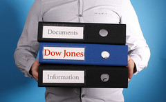 Dow Jones. Businessman is carrying a stack of 3 file folders on blue background