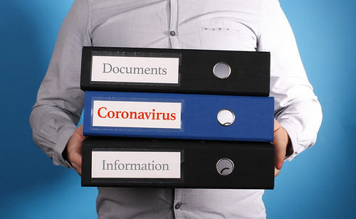 Coronavirus. Businessman is carrying a stack of 3 file folders on blue background | by focusonmore.com
