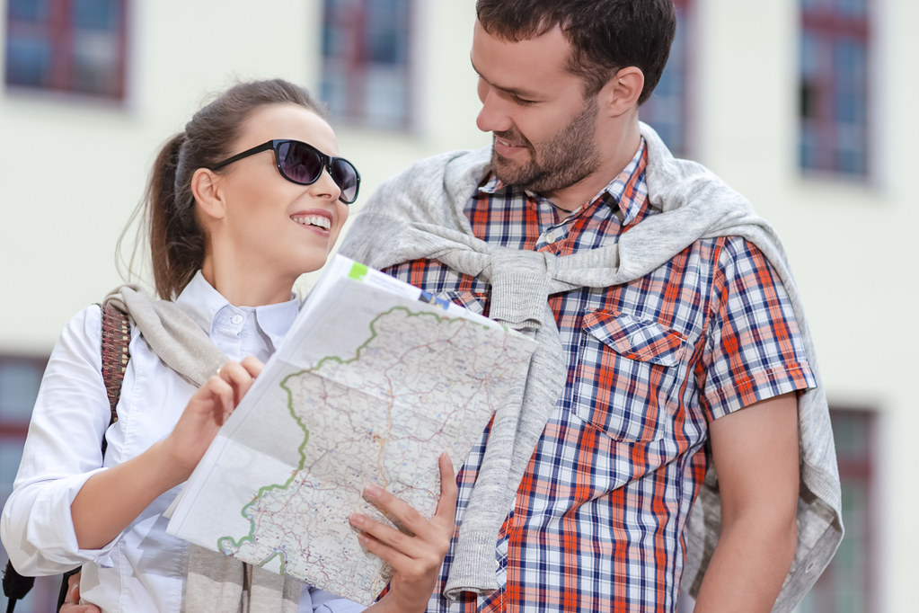 Vacations Ideas. Positive Caucasian Couple Traveling Around City With Camera. Looking for Destination with City Map.