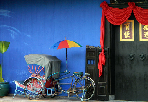 A fully-equipped bicycle rickshaw with a cart and an umbrella, propped up against a blue wall in Penang, Malaysia