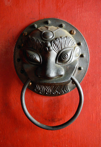 Bronze lion door pull on a red door in the Jetty village in Penang, Malaysia
