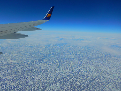 The wing tip with the Icelandair logo flying over frozen wastes