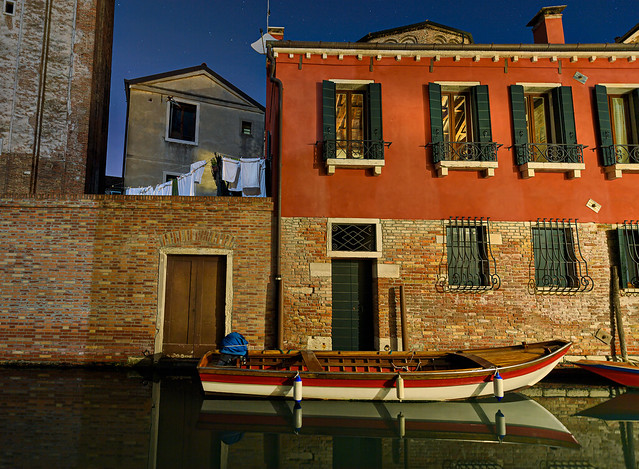 Night scene along a Venice canal with boat reflection and laundry drying, Venice, Italy