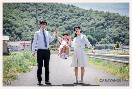 ランドセルを背負った女の子を手で持ちあげるパパとママ