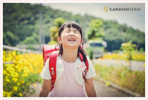 ランドセルを背負った新1年生の女の子 黄色の花を背景に