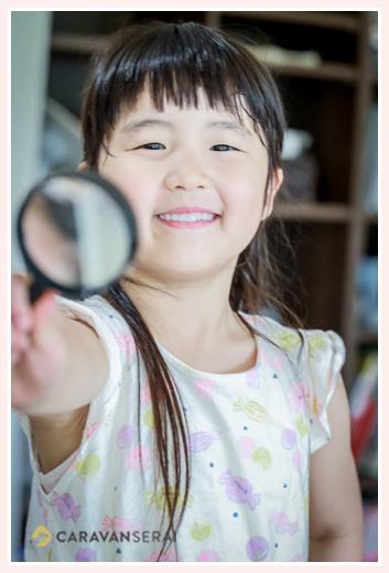 虫メガネを持つ女の子 笑顔